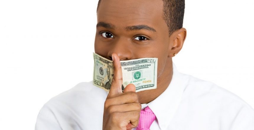 Closeup portrait handsome corrupt guy in shirt, with twenty dollar bill taped to mouth, showing shh sign, isolated white background. Bribery concept in politics, business, diplomacy. Facial expression