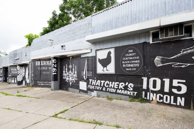 A bold wall of vintage ads recalls Walnut Hills' history of black-owned businesses