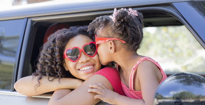 Summer fun! Happy girls or sisters with heart shaped sunglasses in car window. Younger girl kisses older girl on cheek in celebration of love, summer holiday, road trip or Valentines day.