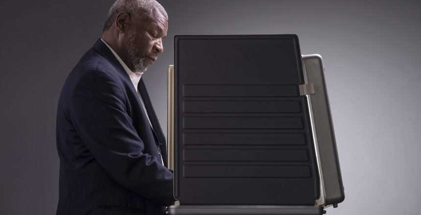 Portrait of a black man standing in a voting booth