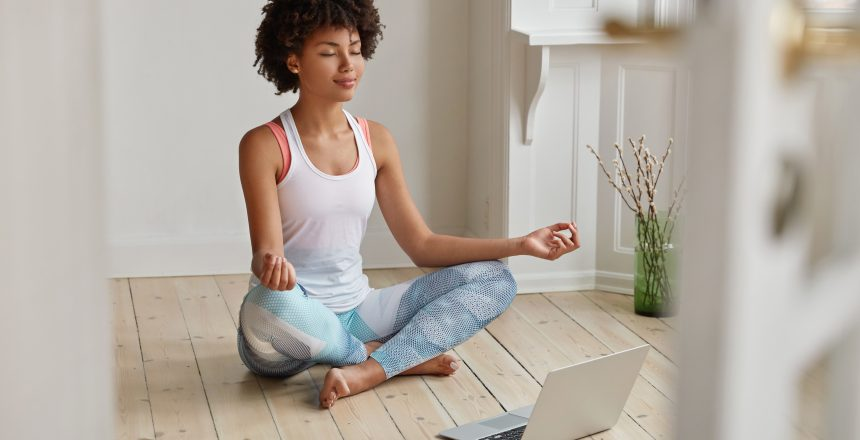 Relaxed dark skinned woman with sporty body, sits in zen pose, keeps legs crossed, watches yoga lessons on laptop computer using internet, meditates on floor in empty room. Wellness concept.