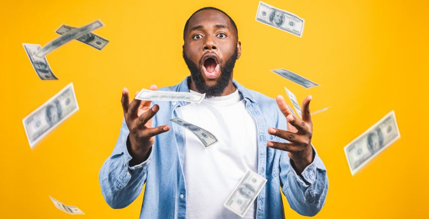 Portrait of a happy young afro american man throwing out money banknotes isolated over yellow background.