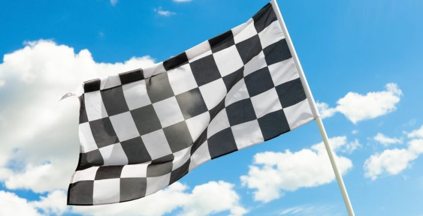 Race flag waving in the wind with white clouds on background - outdoors shoot