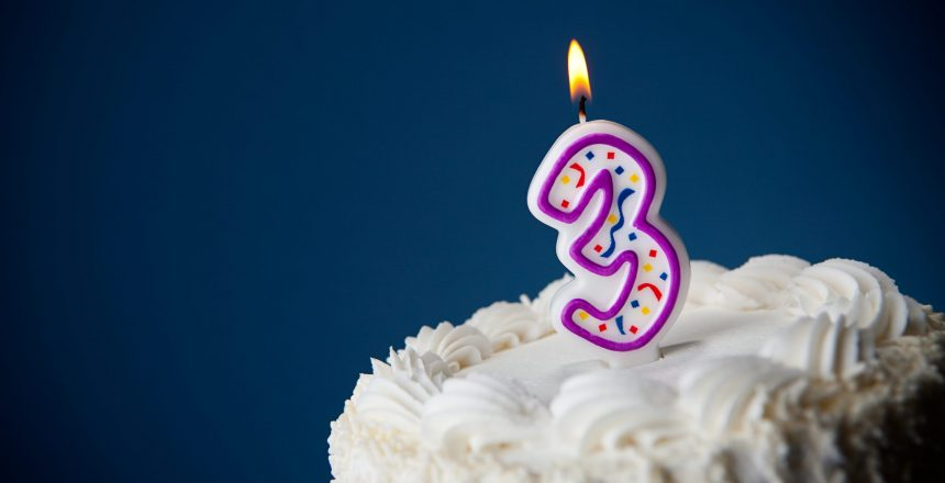 White iced cake on blue background with candles to celebrate various birthdays.