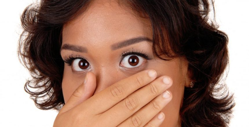 A very surprised mixed raised woman with her hand over her mouth and big eye's, isolated for white background.