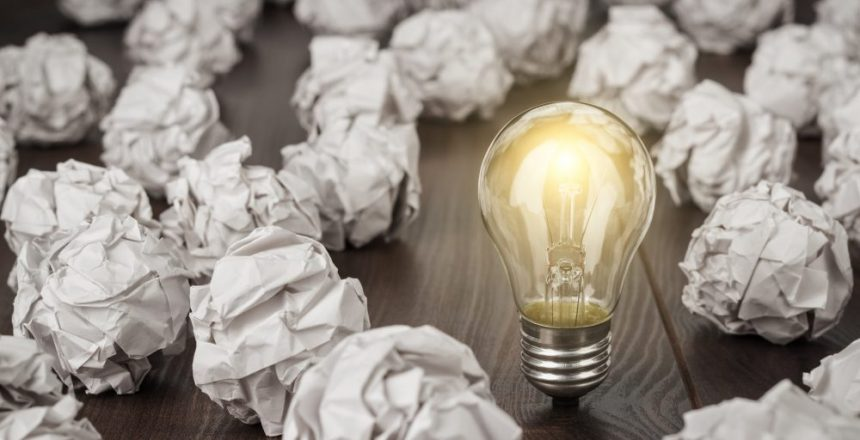 great concept with crumpled office paper and light bulb standing on the table